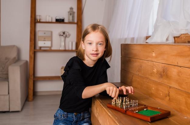 Uma garotinha loira está sentada e jogando xadrez em um tabuleiro. um jogo de lógica