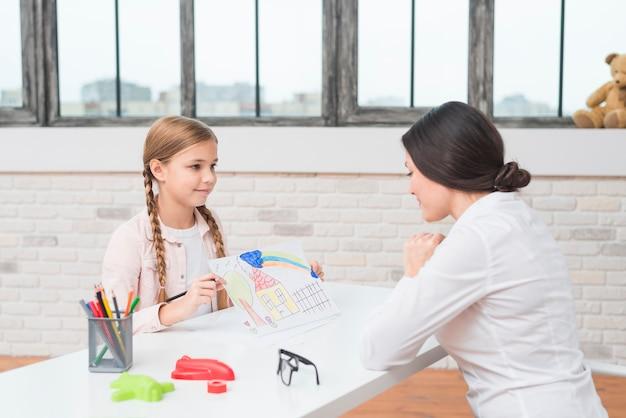 Uma garotinha loira mostrando a casa desenhada no papel para seu psicólogo feminino