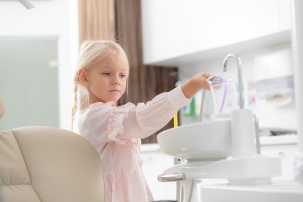 Uma garotinha loira na clínica odontológica.