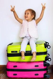 Uma garotinha loira sonha em viajar e senta-se em uma mala