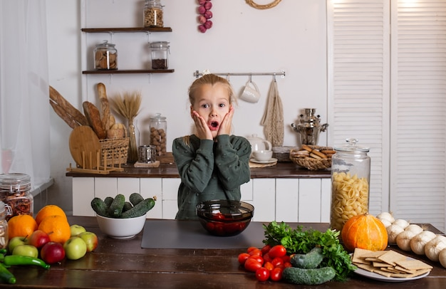 Uma garotinha loira surpresa está sentada à mesa da cozinha com legumes e frutas