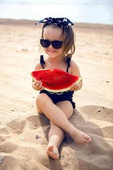Uma garotinha na margem da praia em um maiô preto e óculos pretos, comendo uma suculenta melancia sentada