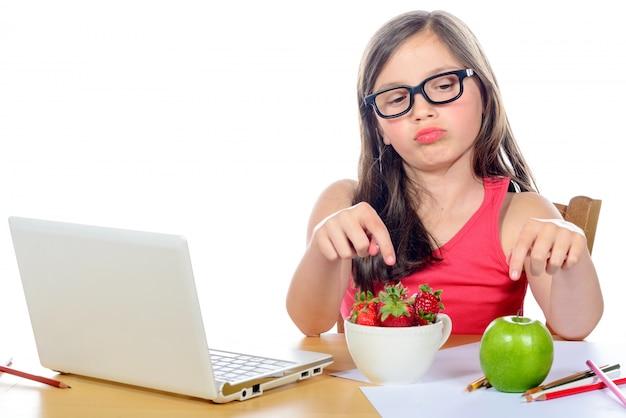 Uma garotinha na mesa dela olhando seu lanche