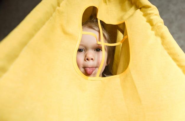 Uma garotinha olha pela janela de uma tenda mostra a língua brincando em casa no sofá. infância feliz
