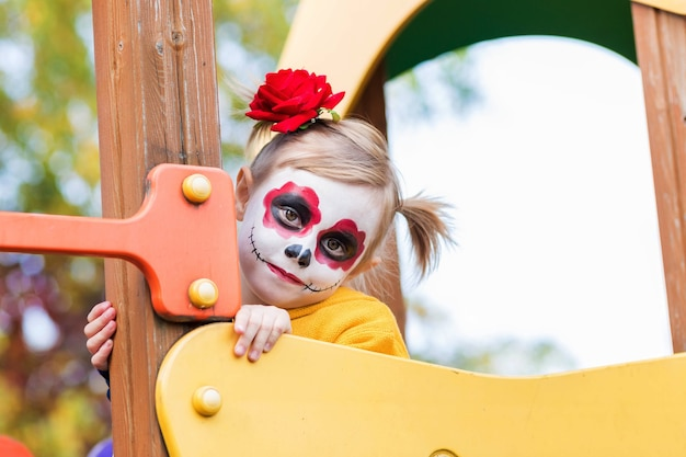 Uma garotinha pré-escolar com o rosto pintado, subiu no escorregador do parquinho, festeja o halloween ou o dia mexicano dos mortos.