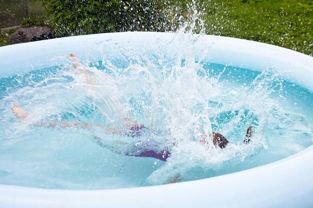 Uma garotinha pula na piscina. forte espirrando.