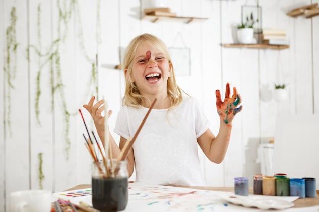Uma garotinha rindo e encantadora, com cabelos loiros, sardas e olhos azuis bagunçou-se de tinta. criança criativa com tinta no rosto e mãos.
