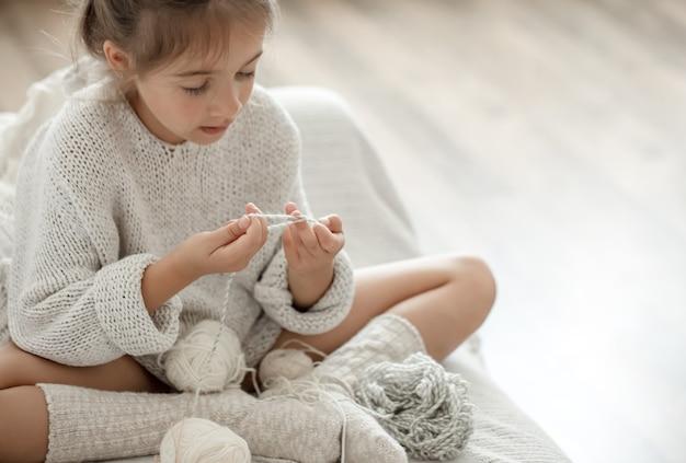 Uma garotinha se senta no sofá com um novelo de linha e aprende a tricotar.