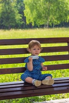 Uma garotinha se senta sozinha em um banco em um parque de verão e tira sua máscara médica