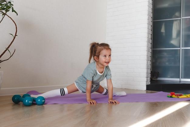 Uma garotinha sentada na divisão durante uma aula de ginástica em casa