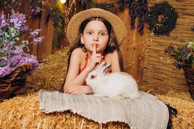 Uma garotinha surpresa em uma fazenda conta um segredo para um coelho branco conceito de feriado de páscoa
