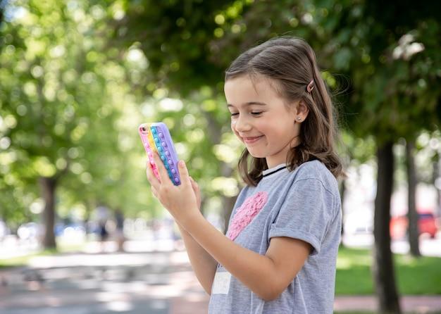 Uma garotinha tem nas mãos um telefone em uma caixa com espinhas estourá-lo, um brinquedo anti-estresse da moda.