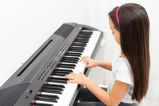 Uma garotinha tocando piano, sintetizador
