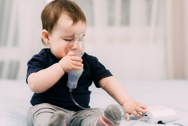 Uma garotinha você mesma segurando a máscara do nebulizador, fazendo inalação e tratando