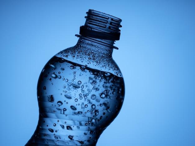 Uma garrafa aberta de água com gás é isolada em um fundo azul