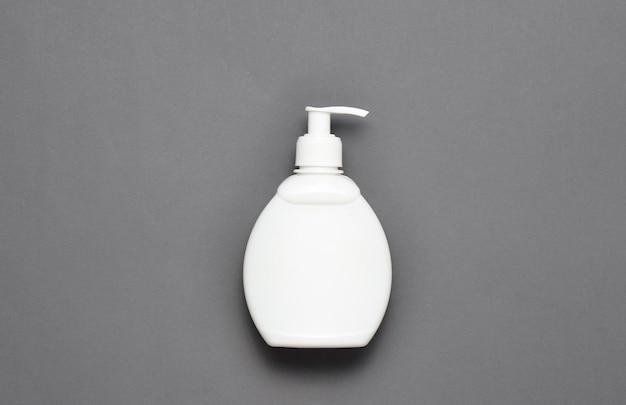 Uma garrafa branca de sabão líquido em um fundo cinza. vista do topo.