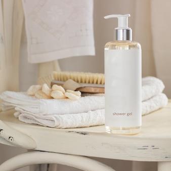 Uma garrafa com gel de banho, uma escova corporal e um par de luvas de banho em uma cadeira branca no banheiro