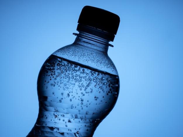 Uma garrafa de água com gás é isolada em um fundo azul