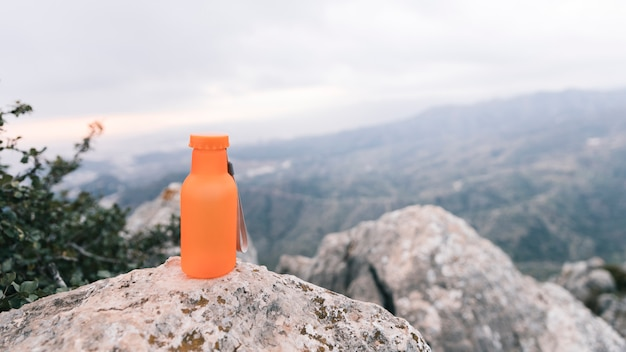Uma garrafa de água de cor laranja no topo da montanha rochosa