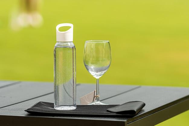 Uma garrafa de água e um copo vazio sobre um fundo desfocado, o conceito da necessidade de usar água