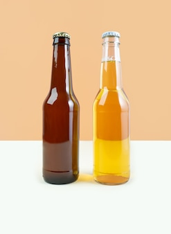 Uma garrafa de cerveja artesanal e cerveja porter em fundo bege de cor dupla. dia internacional da cerveja ou conceitos de octoberfest. cores minimalistas em uma foto. vista frontal.