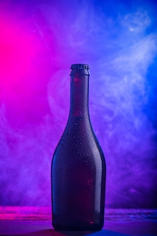 Uma garrafa de cerveja em fundo escuro de fumaça colorida close-up