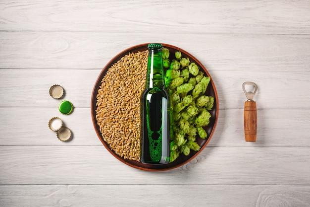 Uma garrafa de cerveja em um prato com lúpulo verde e grão de aveia com abridor e corcks em uma placa de madeira branca
