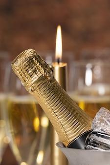 Uma garrafa de champanhe com cubos de gelo e uma vela acesa desfocada na parte de trás. conceito de celebração.
