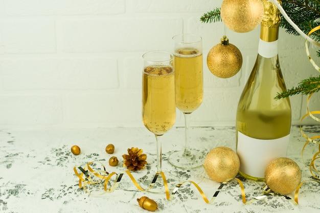 Uma garrafa de champanhe e duas taças de vinho espumante na árvore de natal com bolas douradas em uma mesa branca perto de uma parede de tijolos.