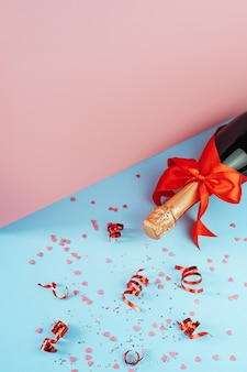 Uma garrafa de champanhe, fitas de férias e decorações em forma de coração encontram-se sobre a mesa em uma vista isométrica. conceito de amor e celebração do dia dos namorados.