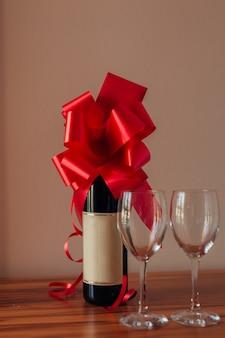Uma garrafa de champanhe na mesa e duas taças vazias