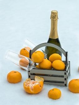 Uma garrafa de champanhe, uma caixa de tangerinas e taças na neve