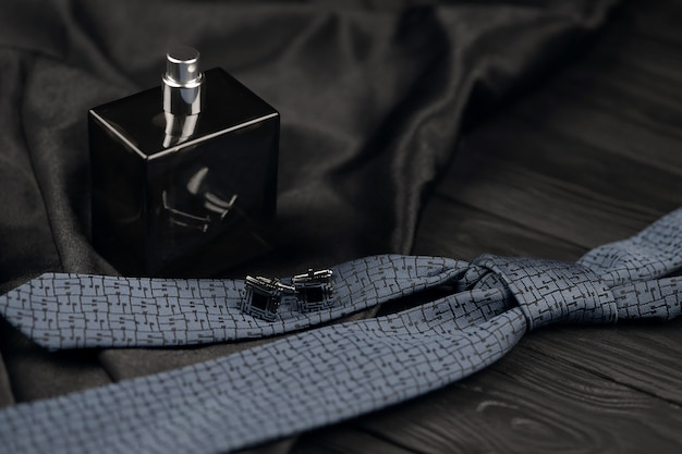 Uma garrafa de colônia masculina e botões de punho com gravata azul mentem sobre um fundo de tecido preto de luxo sobre uma mesa de madeira. acessórios clássicos masculinos. dof raso