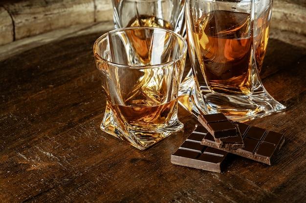 Uma garrafa de conhaque e copo em uma mesa de madeira marrom. conhaque