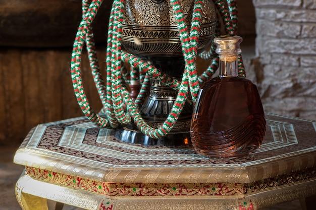 Uma garrafa de conhaque e um narguilé em uma mesa decorativa antiga ricamente decorada