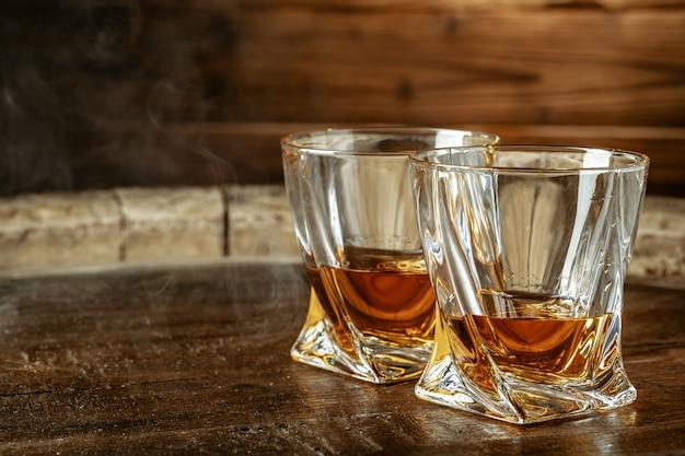 Uma garrafa de conhaque e vidro em um marrom de madeira. conhaque