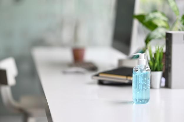 Uma garrafa de desinfetante para as mãos está sendo colocada em uma mesa de trabalho, cercada por vários equipamentos.