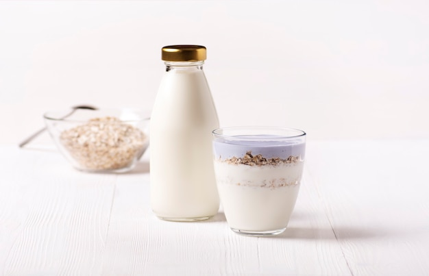 Uma garrafa de kefir caseiro e um copo de kefir e granola estão em uma mesa branca.