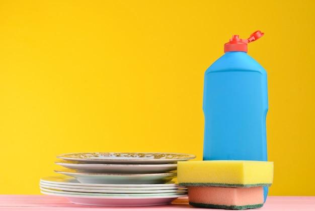 Uma garrafa de lavar louça, esponjas, utensílios sobre uma mesa de madeira de cor pastel, copie o espaço