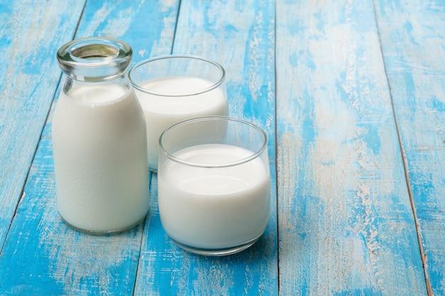 Uma garrafa de leite e copo de leite em uma mesa de madeira azul