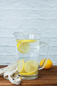 Uma garrafa de limão com limões na superfície de madeira e branca, vista lateral. espaço para texto