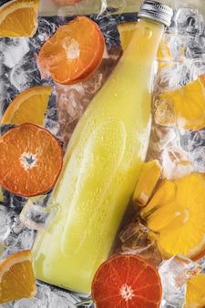 Uma garrafa de limonada refrigerante fresca de verão em água com cubos de gelo