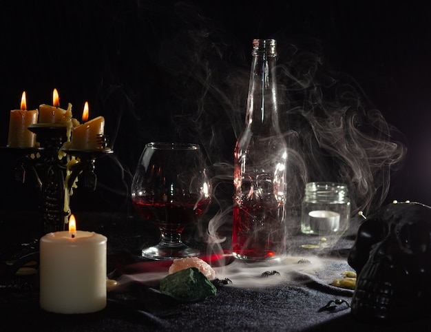 Uma garrafa de líquido vermelho como sangue e um copo