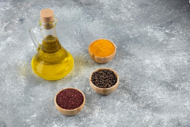 Uma garrafa de óleo com tigelas de madeira com pimentas.