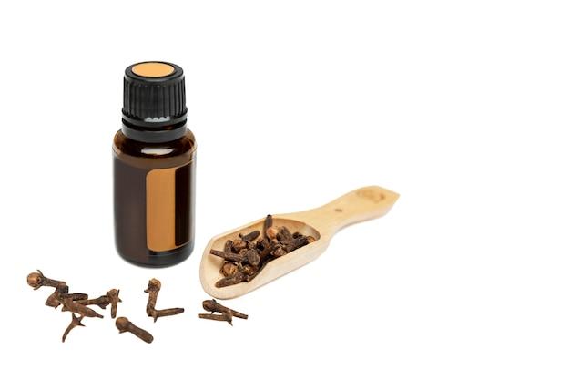 Uma garrafa de óleo essencial com cravo seco espalhado. cosméticos naturais e produtos de saúde da natureza. isolado em um fundo branco. espaço para texto.