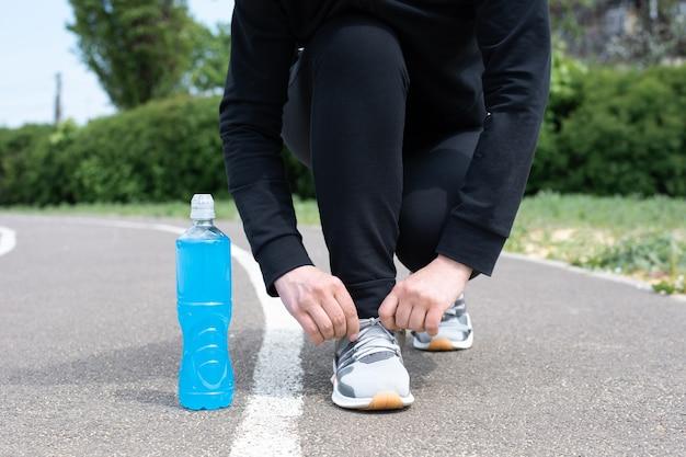 Uma garrafa de plástico azul de bebida isotônica e uma esportista amarrando o cadarço do tênis na pista de corrida, close-up.