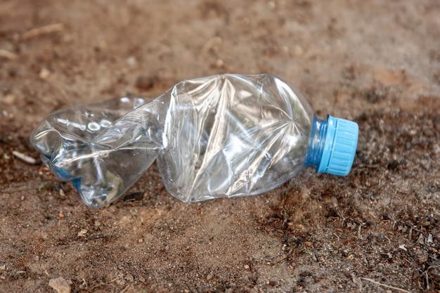 Uma garrafa de plástico está caída no chão. conceito de poluição ambiental.