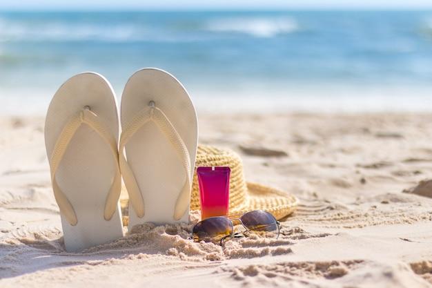 Uma garrafa de protetor solar com óculos de sol, chapéu panamá e chinelo na praia, remédios e proteção para a pele no verão, férias no mar