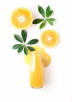 Uma garrafa de suco de laranja fresco encontra-se em uma poça de suco com pedaços de laranja e folhas, vista de cima, de cima.