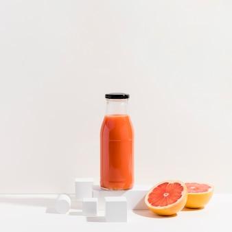 Uma garrafa de suco de laranja vermelho fresco